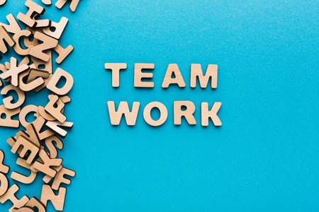 Word Teamwork on blue background. Cooperation, togetherness, partnership concept Stock Photo