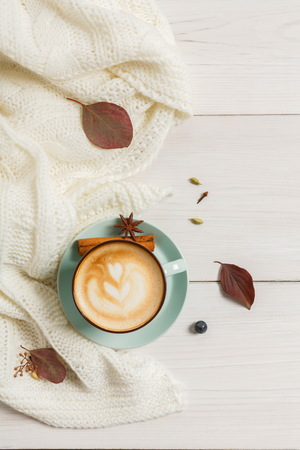 Autumn morning composition background. Blue coffee cup with hot foamy cappuccino top view, cloves, cinnamon and warm sweater at white wood. Fall spicy drinks concept, copy space
