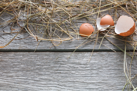 Fresh chicken eggs background. Brown eggshall on hay at rustic wood table. Top view with copy space. Rural still life, natural healthy food and organic farming concept.