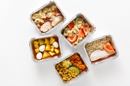 Pasti quotidiani sani, consegna del cibo. Togliere i piatti di fitness naturale per la dieta. Pranzo in scatole di alluminio su sfondo bianco