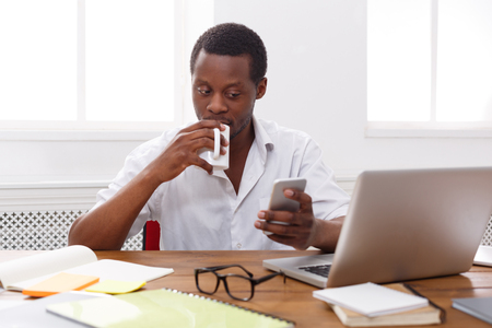 Young black employee at workplace. Checking social media on smartphone while coffee break Stock Photo