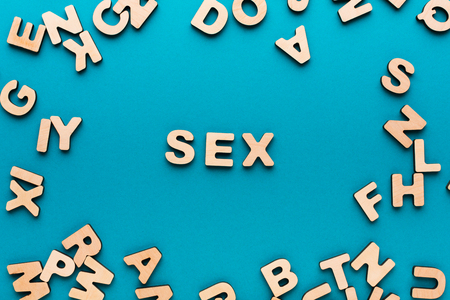 educacion sexual: Word Sex in wooden letters frame on blue background. Couple relationship, satisfaction, romance concept