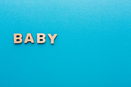 Word Baby made with wooden letters on blue background, copy space