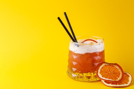 citrons: Cocktail on juicy orange background. Citrus alcohol beverage with tequila, blood orange juice and ginger beer, served with citrons and straws, copy space