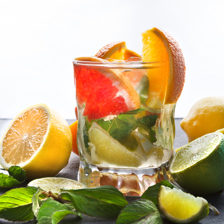 Summer citrus drink on white background. Healthy detox water in glass and fruits variety on gray table. Colorful backdrop with oranges, lemon and lime, copy space, closeup