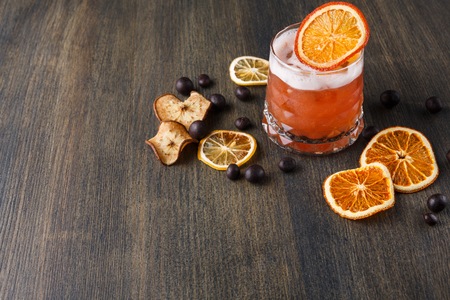 citrons: Cool alcohol cocktail at wooden background. Blood orange margarita with tequila on rustic table with citrons and chocolate snacks. Bar and restaurant backdrop with copy space for drinks menu