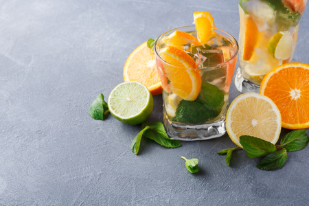 Summer citrus drinks background. Detox water in glasses and fruits variety on gray table. Colorful backdrop with oranges, lemon and lime, copy space. Bar beverages or healthy eating dietary concept