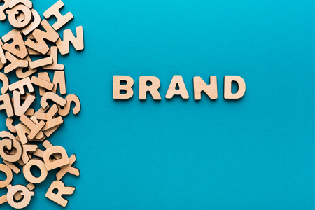 english letters: Word Brand on blue background. Famous name, trendy goods, tendency concept Stock Photo