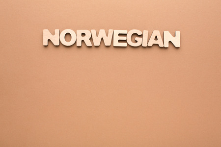 english letters: Word Norwegian on beige background. Foreign language learning, education concept