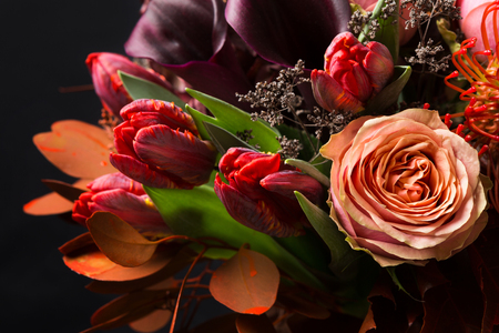 concep: Colorful fall bouquet on black background. Autumn composition of roses, tulips, dry leaves and herbs closeup. Flower shop and florist design concep Stock Photo