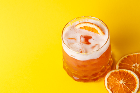 citrons: Cocktail on juicy orange background. Citrus alcohol beverage with tequila, blood orange juice and ginger beer, served with citrons and ice, copy space