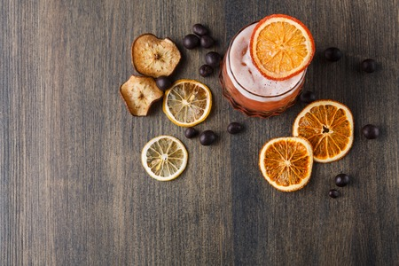 citrons: Cocktail on rustic wood background. Cold citrus alcohol beverage with tequila, blood orange juice and ginger beer, served with ice, citrons and chocolate snacks, top view, copy space