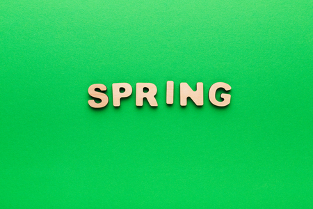 Word Spring made of wooden letters on green background. Season planning, timetable concept Stock Photo