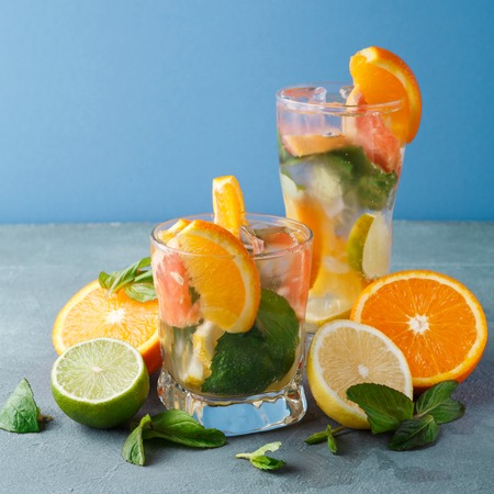 Summer citrus drinks at blue background. Detox water in glasses and fruits variety. Colorful backdrop with oranges, lemon and lime, copy space. Bar beverages or healthy eating dietary concept