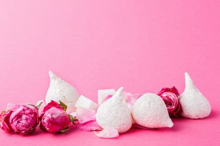 Sweets and flowers at pink background. French meringues and rose buds wallpaper with copy space. Restaurant and patisserie mockup for snack menu Stock Photo