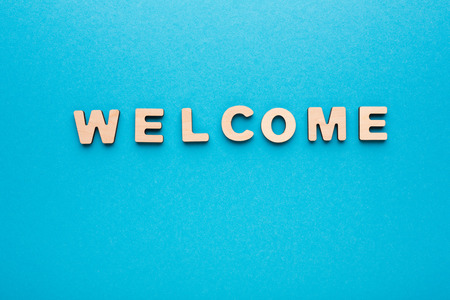 english letters: Word Welcome on blue background. Greeting, hospitality, politeness concept