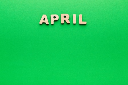 Word April made of wooden letters on green background. Month planning, timetable concept