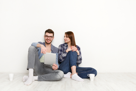 Couple surfing the web and smiling. Man and woman looking through funny content on digital tablet, white background, studio shot