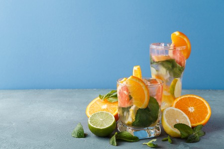 Summer citrus drinks background. Healthy detox water in glasses and fruits variety on gray table over blue wall. Colorful backdrop with oranges, lemon and lime, copy space Stock Photo