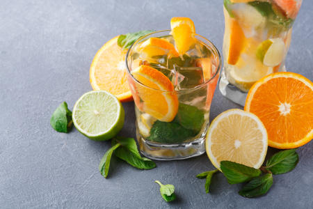 Summer citrus drinks background. Healthy detox water in glasses and fruits variety on wooden board on gray table. Colorful backdrop with oranges, lemon and lime, copy space Stock Photo