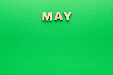 Word May made of wooden letters on green background. Month planning, timetable concept Stock Photo