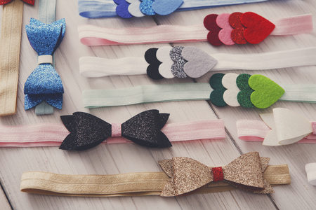Set of colorful elastic decorated headbands. Bright handmade hair accessories with felt bow and star decoration, filtered image. Beauty, fashion, style concept