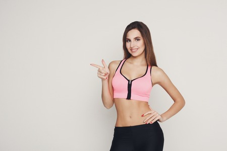 Smiling sporty woman point away. Young beautiful fitness girl gesturing aside of her