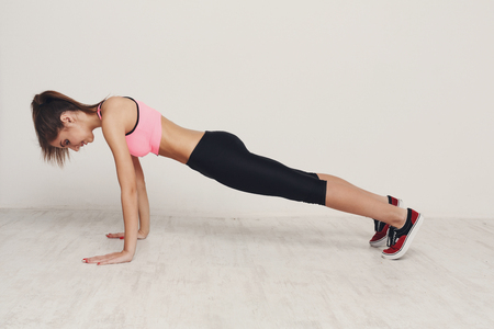 Fitness woman plank workout training at white background indoors. Young slim girl makes exercise. Healthy lifestyle, gymnastics concept Stock Photo