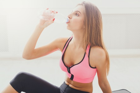 Beautiful young sport woman drinking water. Confident fitness girl holding plastic bottle, thirsty after training, healthy lifestyle concept Stock Photo