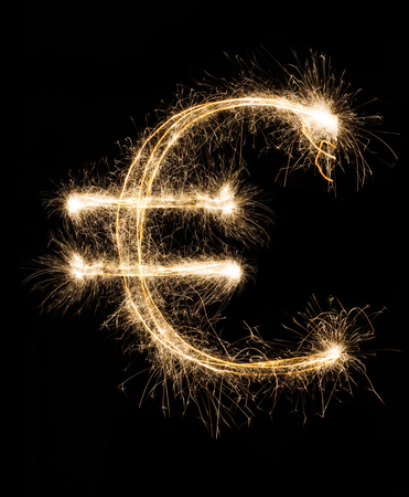 Money and finance business concept. Euro symbol from christmas shining sparkler firework on black background