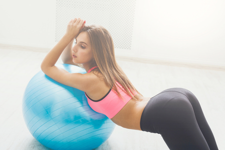 Young woman doing fitness exercises with fit ball at gym. Fitness girl makes buttocks exercises. Weightloss, bodybuilding, beauty concept