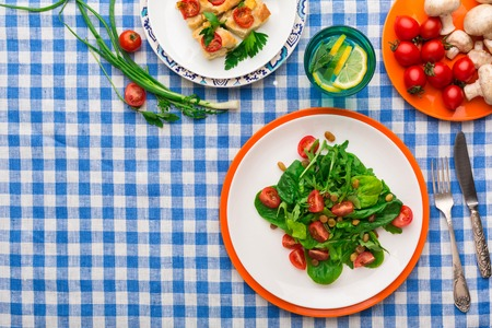 Healthy eating concept. Fresh salad with greens, tomatoes and mushrooms, casserole and lemonade on checkered tablecloth background. Organic vegetables top view, copy space. Stock Photo