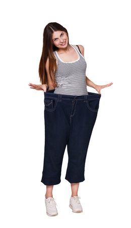 Young woman wearing jeans much bigger size after loosing weight from diet, healthy eating, isolated on white background. Stock Photo