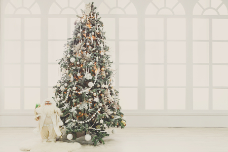 Christmas magic background. Beautiful decorated xmas tree in living room. Shining lights, balls, baubles, garland and toy snata. Winter holidays atmosphere. Modern design and decorations, copy space