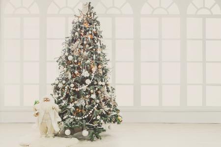Weihnachtszauberhintergrund. Schöner verzierter Weihnachtsbaum im Wohnzimmer. Leuchtende Lichter, Kugeln, Kugeln, Girlande und Spielzeug Snata. Winterurlaub Atmosphäre. Modernes Design und Dekorationen, Textfreiraum