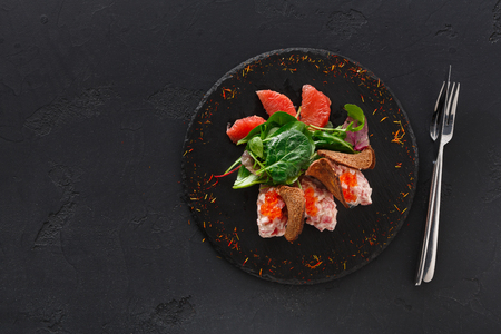 Gourmet seafood snack on black plate top view. Appetizing meal with red salmon, caviar and crispy toasts, restaurant serving Reklamní fotografie