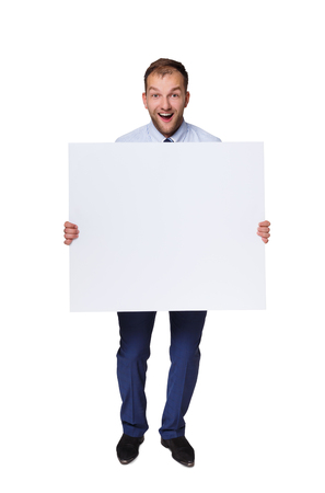 Happy young businessman showing blank signboard with copy space for text or slogan isolated on white background Stock Photo