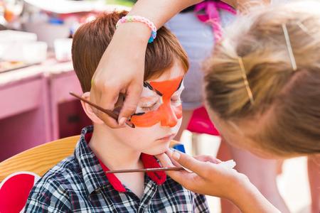 art de visage pour petit garçon. yeux Tiger peinture. divertissement fête d'anniversaire d'enfants, artiste faisant le maquillage drôle