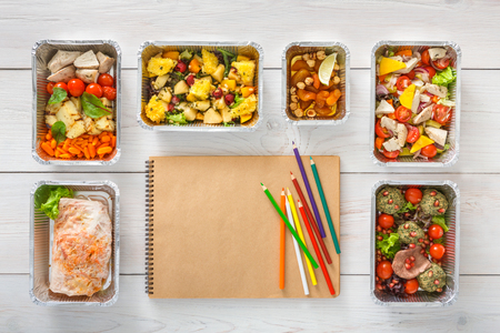 Diet plan with healthy restaurant food delivery. Natural organic fitness nutrition. Daily meals in foil boxes with copy space on craft paper notebook. Top view, flat lay Foto de archivo