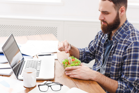 Side view of young tired male IT manager at working place with vegetable salad in bowl, diet and eating right concept. Crop