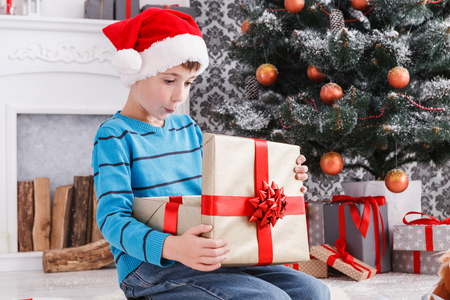 christmas gift: Cute surprised boy in santa hat unwrap christmas present on holiday morning in beautiful room interior. Male child open Xmas gifts near big decorated fir tree and fireplace. Winter holidays concept Stock Photo