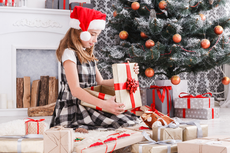 christmas gift: Beautiful happy girl in santa hat unwrap christmas present box on holiday morning in beautiful room interior. Female child open Xmas gift near decorated fir tree and fireplace. Winter holidays concept