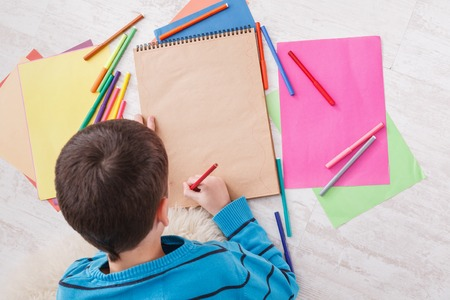christmas gift: Writing letter to santa. Cute boy makes wish list of presents for christmas. Drawing picture. Prepare for winter holidays, top view of child on floor
