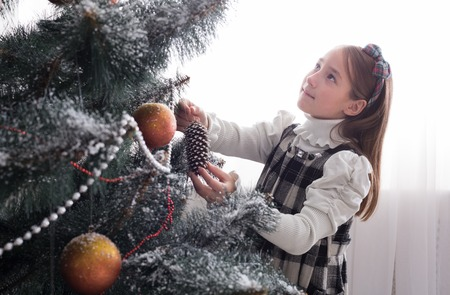 decorate: Pretty little girl decorate big christmas tree. Child prepare to winter holiday, hang decorations, tinsel, bead garland, ornaments, baubles and balls. Christmas atmosphere at cosy home