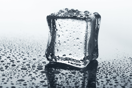 drop water: Transparent ice cube with reflection on white background. Closeup of cold crystal block on glass with water drops Stock Photo