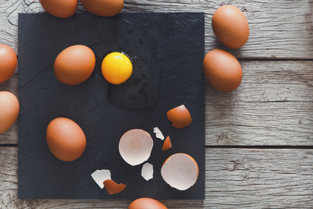 heap: Fresh chicken brown home eggs top view with cracked eggshell and yolk on rustic slate black plate on wood background. Natural healthy food and organic cooking ingredients Stock Photo