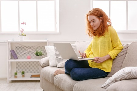 Cute redhead freelancer girl working on laptop. Young woman in casual sitting on beige couch in light appartment Stock Photo
