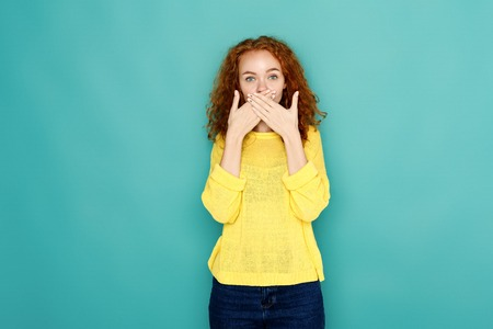 Keep silence. Redhead woman covering mouth with hands while posing to camera on blue studio background. Girl close lips with palms, speak no evil concept Stock Photo