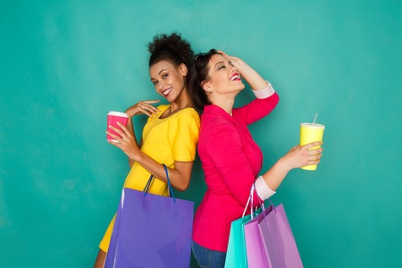 Happy multiethnic girlfriends with shopping bags and take away drinks. Two excited shopaholics at turquoise sudio background with copy space