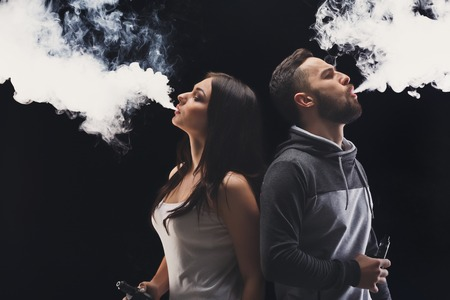 Couple vaping. Young man and woman blowing smoke at black studio background. Relationship and vape addiction concept with copy space